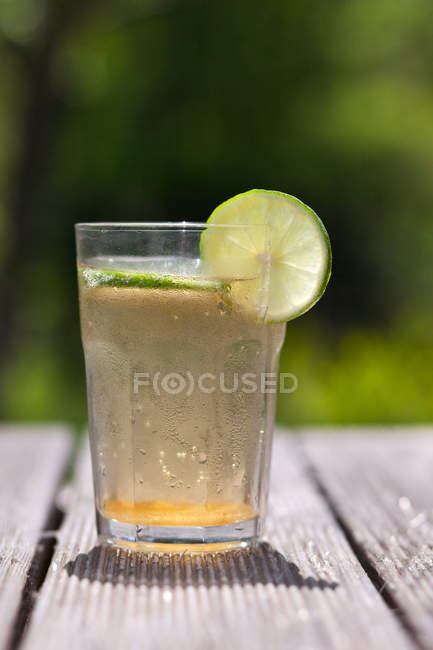 Glass of Sparkling water with fresh lime slices, blurred background — Stock Photo