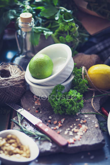 Citron vert et fines herbes sur la planche à la cuisine — Photo de stock