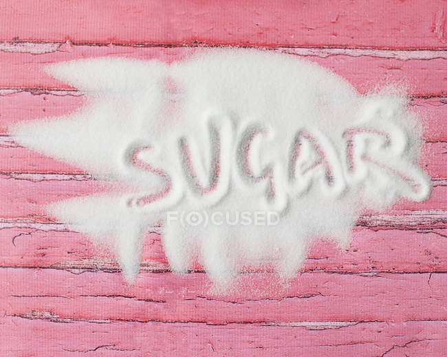 Word sugar written in sugar on pink wooden table — Stock Photo
