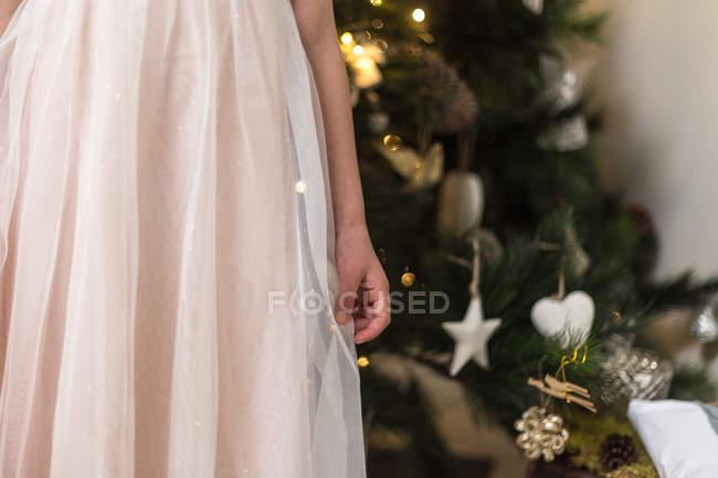 Immagine ritagliata di vita giù colpo di una ragazza in rosa in piedi davanti all'albero di Natale — Foto stock