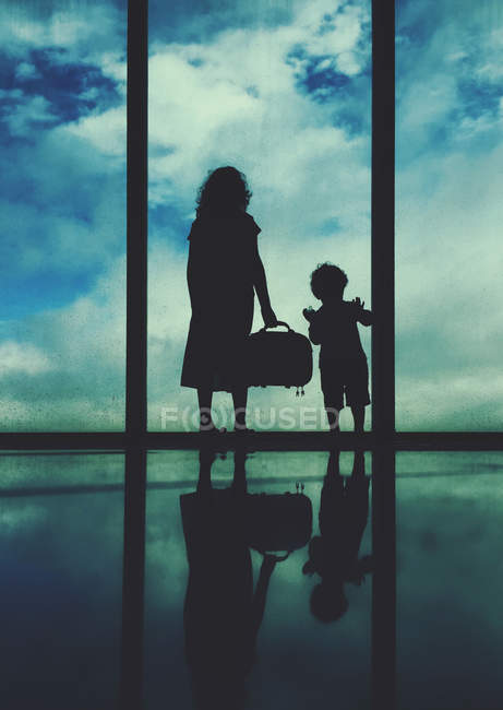 Silhouette of a woman and boy standing at an airport window — Stock Photo