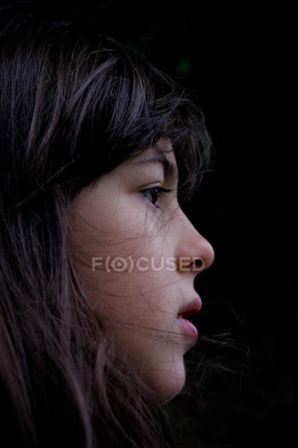 Profile of pensive girl with dark hair on black background — Stock Photo