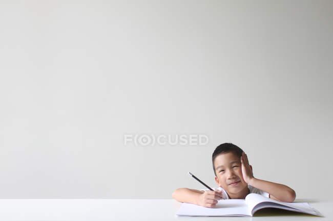 Boy sitting with notebook studying on white background — Stock Photo