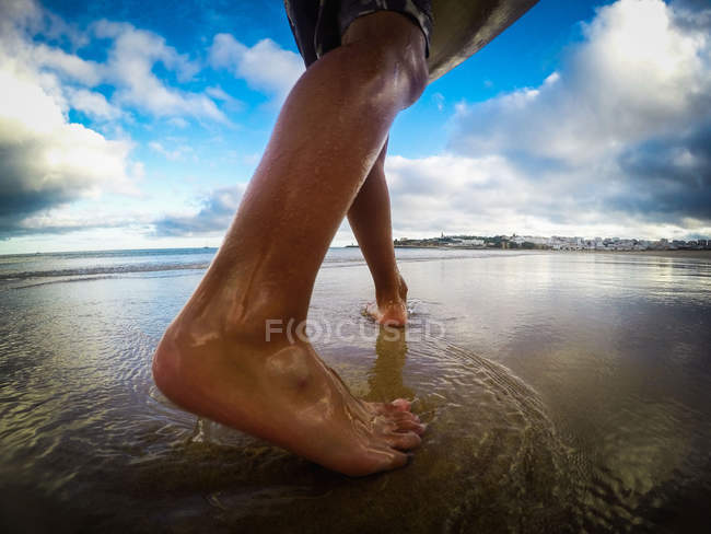 Low section of a boy walking on beach — Stock Photo
