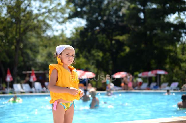Ragazza in piedi vicino alla piscina indossando un giubbotto di salvataggio — Foto stock