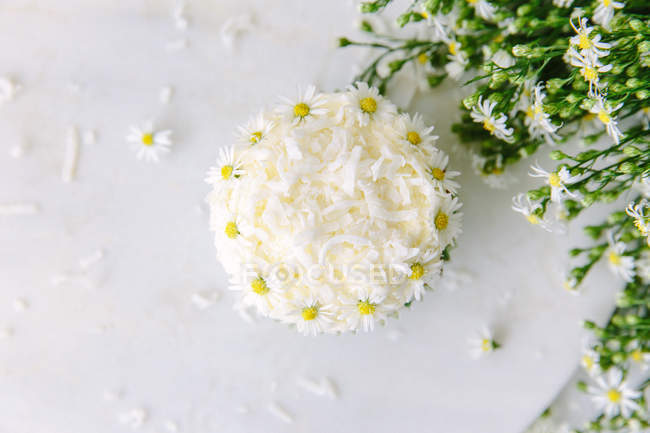 Elevated view of a cupcake decorated with daisies — Stock Photo