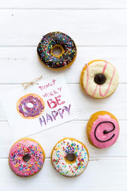 Selección de donuts con glaseado multicolor con nota - foto de stock