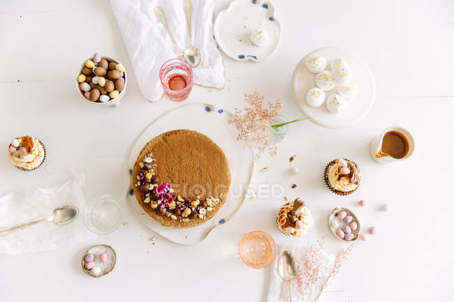 Afternoon tea table setting with cake, chocolate sauce, chocolate eggs and meringues — Stock Photo