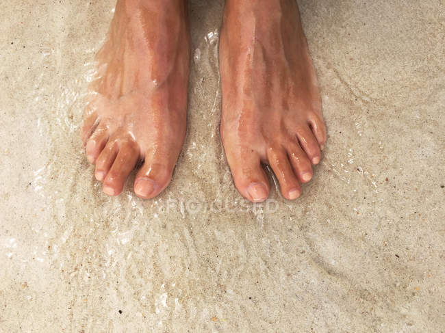 Close-up of female Feet on sand in sea — Stock Photo