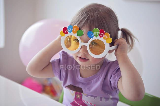 Девочка в очках на день рождения — стоковое фото