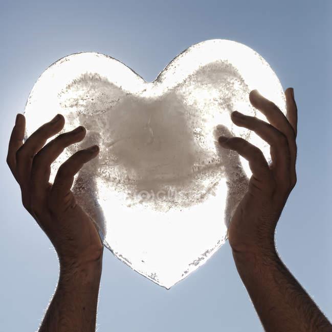 Кадроване зображення особою, заморожених серце проти неба — стокове фото
