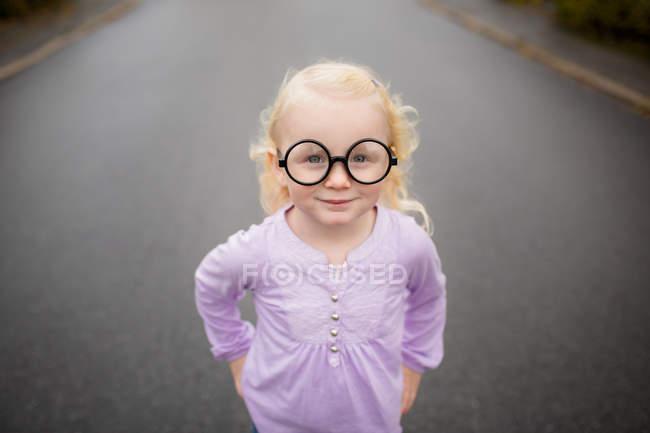 Ritratto di una ragazza che indossa occhiali stupidi in piedi sulla strada — Foto stock