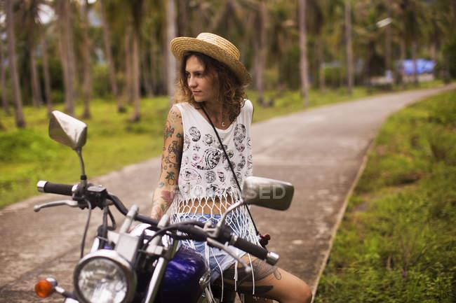 Kantige tätowierte Frau sitzt auf einem Motorrad — Stockfoto