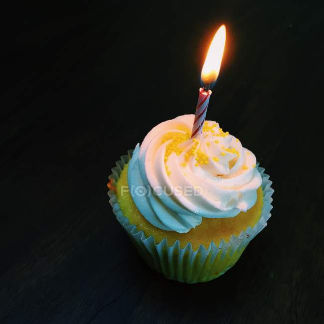 Cupcake with a lonely candle against black background — Stock Photo