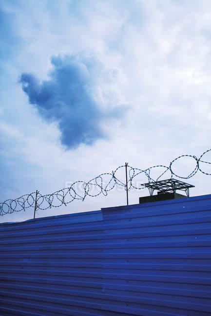 Nuvens acima da cerca de arame farpado na prisão — Fotografia de Stock