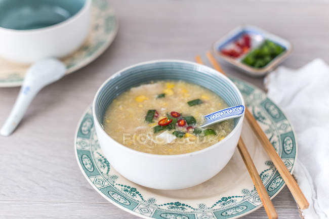 Chinese Chicken and sweetcorn soup over wooden background — Stock Photo