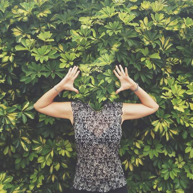 Woman with face hidden behind leaves standing with raised arms — Stock Photo