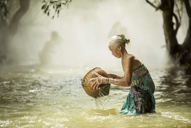 Vista laterale della donna maggiore pesca in torrente in Thailandia — Foto stock