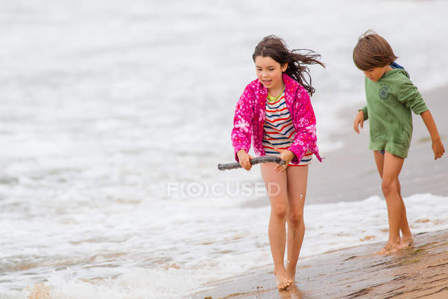 Boy and girl walking on the beach — Stock Photo
