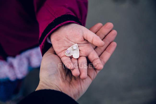Обітнутого зображення мати і дочка руки, що тримає на об'єкт у формі серця — стокове фото