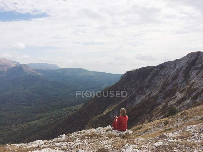 Rear view of a woman sitting on mountain and looking at view — Stock Photo