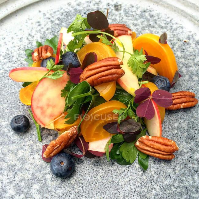 Nahaufnahme von Rote Beete, Pekannuss, Heidelbeere, Apfel und Petersilie Salat auf graue Platte — Stockfoto