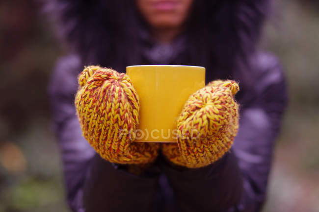 Close-up of female Hands wearing gloves holding cup of tea — Stock Photo