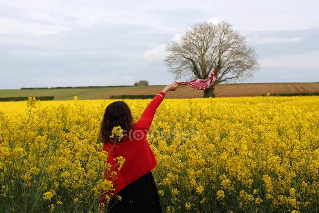 Woman waving scarf in rapeseed field, Niort, France — Stock Photo