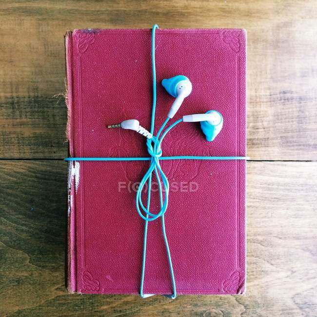 Audio book concept, headphones wrapped around an old book — Stock Photo