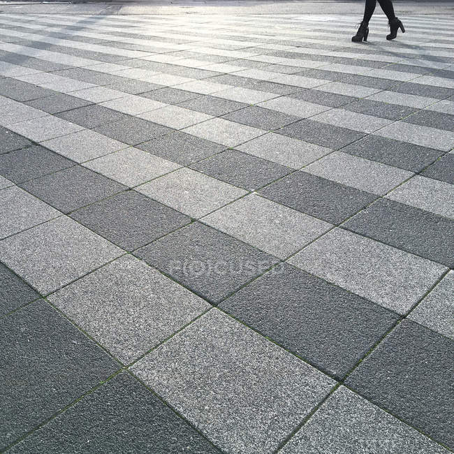 Female legs walking in street with tiles — Stock Photo