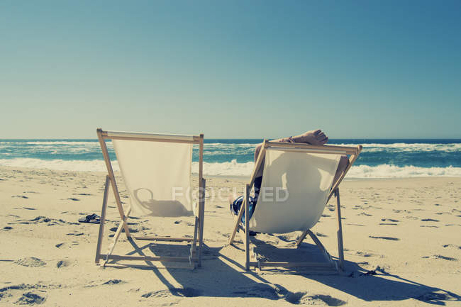 Relaxed man sitting in deckchair on the beach — Stock Photo