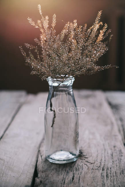Glass Bottle with wildflowers on wooden table — Stock Photo