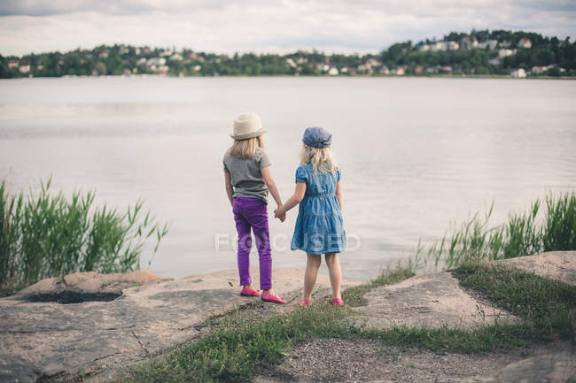 Two cute sisters holding hands and looking at lake — Stock Photo