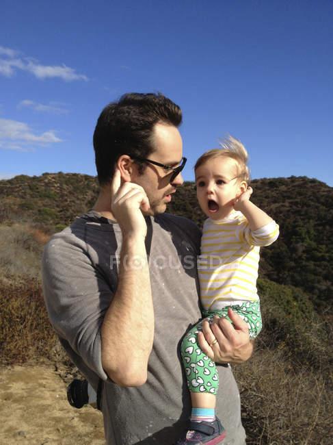 Pai e filha de mãos dadas para os ouvidos e ouvir golpes de vento — Fotografia de Stock