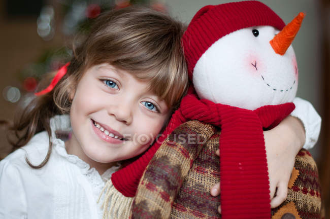 Portrait of smiling cute girl with snowman — Stock Photo