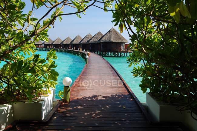 Vista panoramica di lungo ponte pedonale sopraelevato che conduce attraverso l'acqua a fila di capanne a palafitte, Maldive — Foto stock