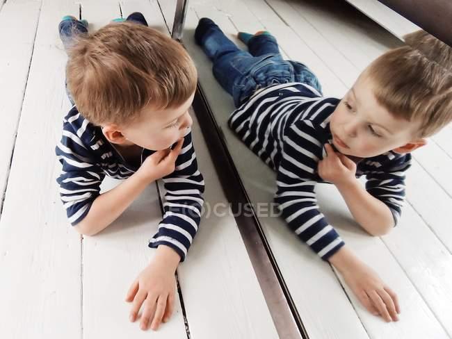 Портрет гарний маленький хлопчик лежав на підлозі, дивлячись на себе в дзеркало — стокове фото
