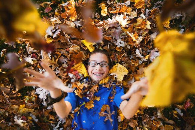 Boy lying on back and playing with autumn leaves — Stock Photo
