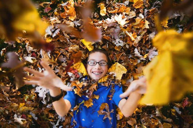 Menino deitado de costas e brincando com folhas de outono — Fotografia de Stock