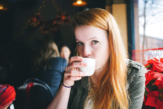 Ritratto di giovane donna che sorseggia da una tazza bianca nel ristorante — Foto stock