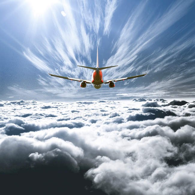 Majestic view of airplane flying above the clouds — Stock Photo