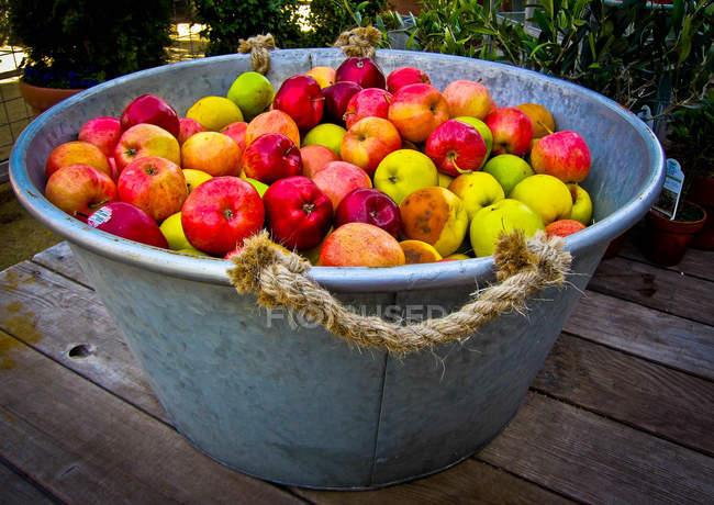 Tubful di mele su tavolo di legno all'aperto — Foto stock