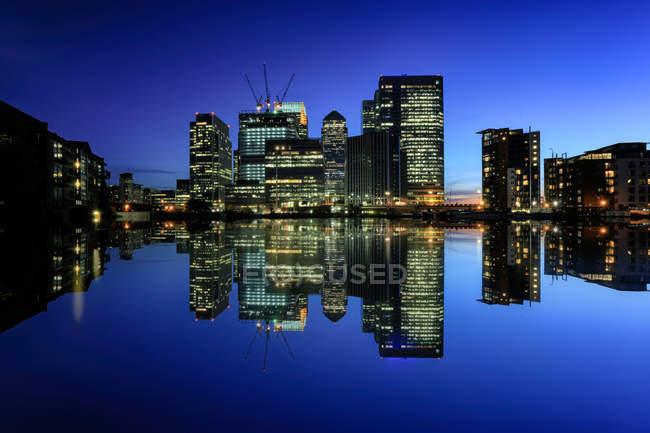Grattacieli illuminati che riflette in ancora fiume, Canary Wharf, Londra, Regno Unito — Foto stock