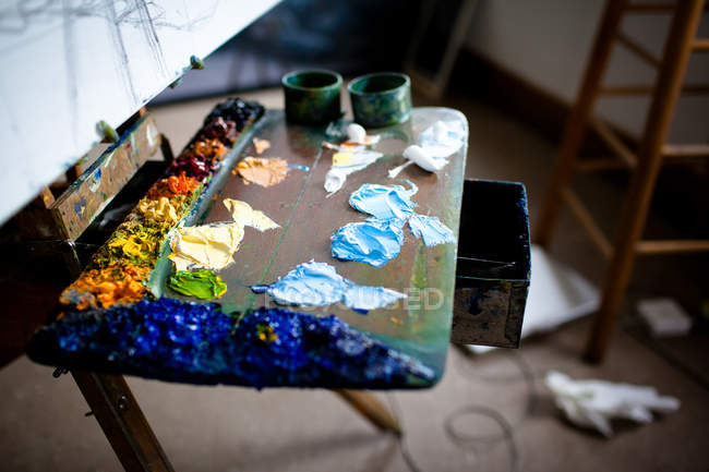 Elevated view of painter workplace with palette and easel — Stock Photo
