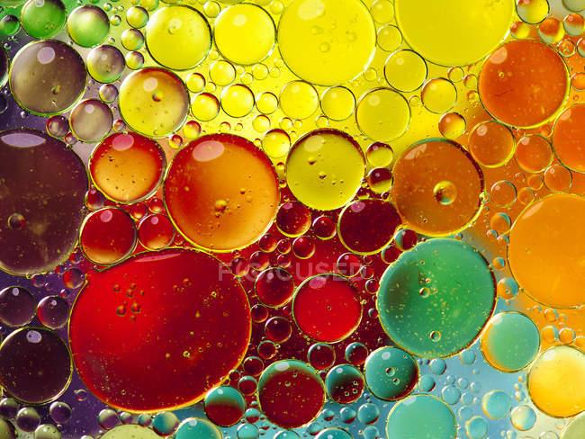 Vista de cerca de burbujas de aceite de colores en el agua - foto de stock