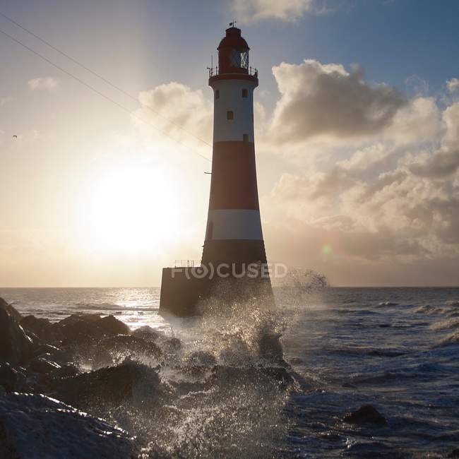 Beachy Head Lighthouse against sunrise with surf splashing against rocks in foreground, East Sussex, UK — Stock Photo