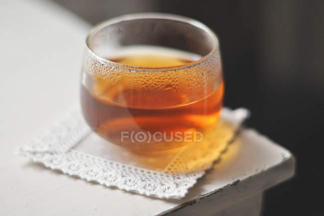 Glass of tea on square napkin on corner of table — Stock Photo
