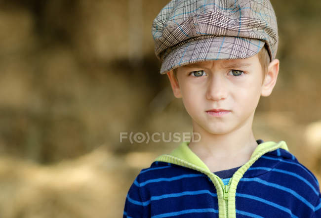 Portrait of serious little boy wearing hat standing outdoors — Stock Photo