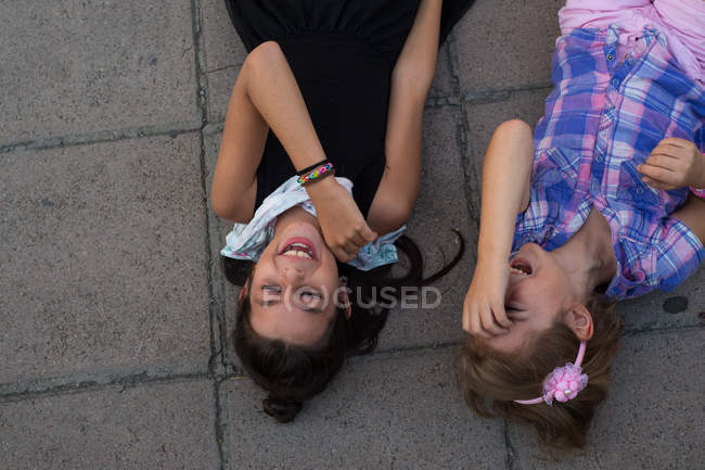 High angle view of two cute sisters lying on floor and laughing — Stock Photo