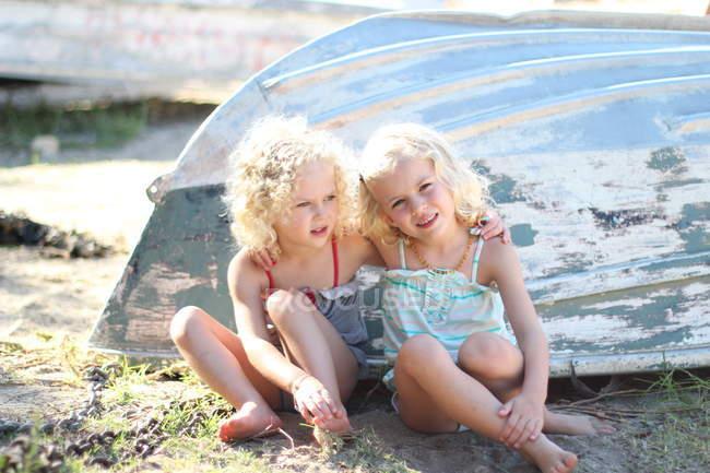 Девушки сидят на песчаном пляже — стоковое фото